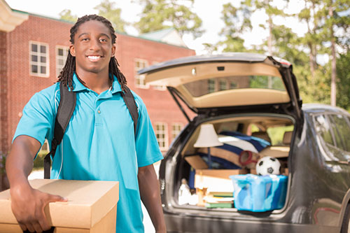 Young male heads off to college. The 18-year-old is unpacking his car as he moves into the college campus dorm. He is excited to start his school adventures. He carries a backpack and moving box. Back to school.