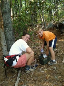 Shown here are a mother (30 something) and her six-year-old son finding a hidden treasure while geocaching in the woods. Geocaching is a treasure hunting game where you use a GPS to hide and seek containers with other participants in the activity. All logos removed.
