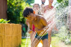 Family cooling down with sprinkler in garden