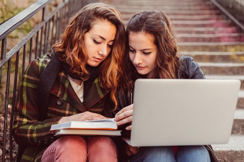 Schoolgirls studying on the lap top outside