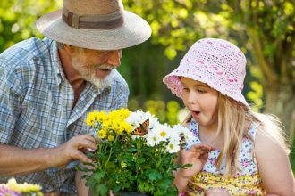 Grandfather with his granddaughter watching a butterfly together