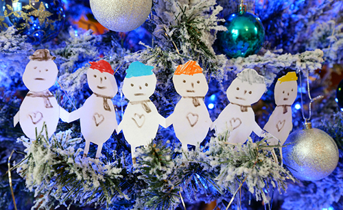 A depiction of a family with cut out paper people on a blue themed Christmas tree.