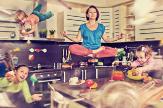 Mother meditating at the kitchen with her children flying around
