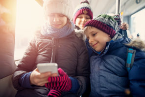 Mom and kids looking at a smartphone in winter gear