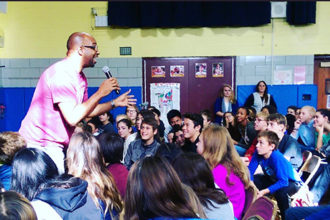 Author Kwame Alexander talking to students at a school