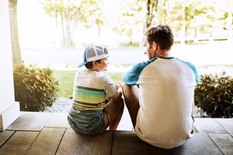 Rearview shot of a father and his son bonding on their porch at home