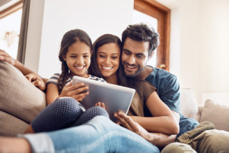 Shot of a mother and father using a digital tablet with their daughter on the sofa at home