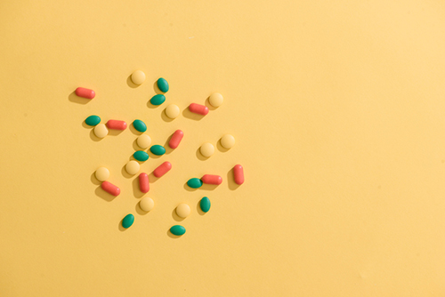 Opioids - Colorful pills on yellow background
