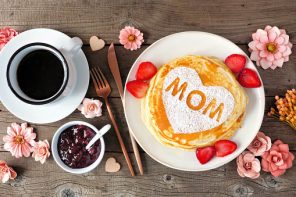 Show Mom Love! Pancakes with heart shape and MOM letters. Mother's Day breakfast concept. Overhead view table scene with a rustic wood background.