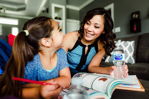 Mom and daughter practice healthy hydration by drinking Nestlé Water.