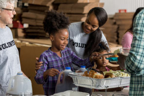A young mother and her two little girls serve a healthy meal to people in a homeless shelter.