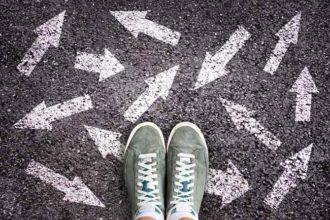 how to pick the right college - Sneaker shoes and arrows pointing in different directions on asphalt ground, choice concept