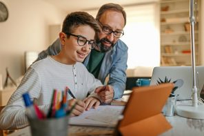 Keeping kids engaged in learning: Father embracing son from behind while helping him with homework