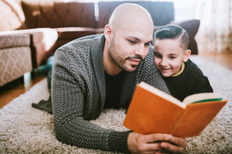 A millennial father and his boy lay on a rug on the living room floor, reading a book together. A good teaching opportunity as the child is learning to read. The dad smiles as he reads, the son looking on attentively.