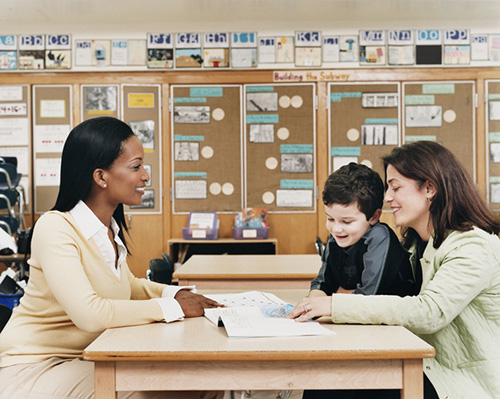 Asking the right questions: Teacher Sitting at a School Desk Showing a Book to a Parent and Her Son