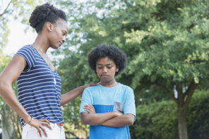 How to handle bad habits ... Mother standing outdoors with her 12 year old son. She is looking at him with a disapproving expression. He is looking down with has arms folded, caught doing something he wasn't supposed to do.