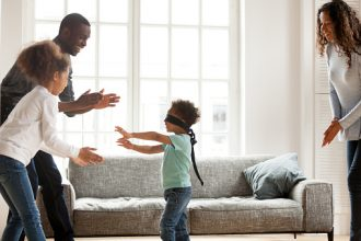 Family Fun Activities: Funny little blindfolded boy play hide and seek game with mixed race family in living room, toddler have fun with black parents and sister, spend time together laughing entertaining at home
