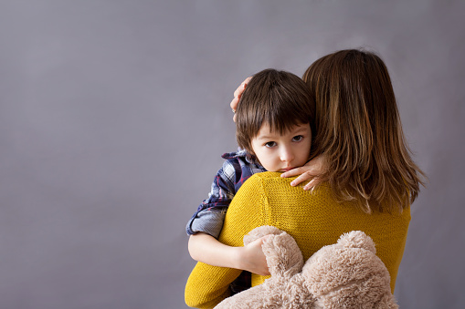 Manage anxiety: Sad little child, boy, anxiety, hugging his mother at home