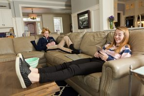 Social distancing teens on social media A boy and a girl using their mobile phone and WIFI at their home living room.