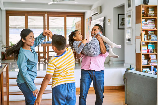 Routine Healthy Habits: Happy woman dancing with son in living room. Smiling father carrying daughter. They are spending leisure time.