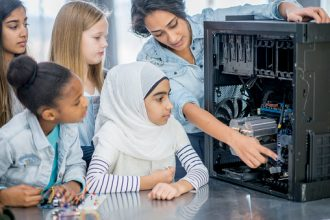 STEM Careers: A group of elementary school children and their teacher and indoors in their classroom. The female teacher has opened a desktop computer to view the inside components. She is pointing to certain parts and explaining what they do.