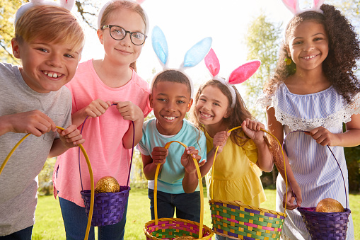 Portrait Of Five Children Wearing Bunny Ears On Easter Egg Hunt In Garden Passover