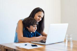 Young mother and son sitting at table and using laptop at home. Smiling mom working at home with her child on the knees while writing an email. Young woman teaching little boy to use the computer.
