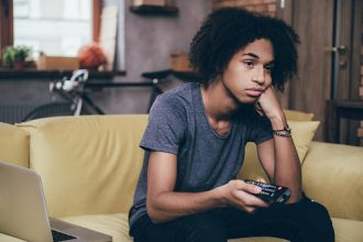 Missed Milestones: Young African man holding remote control and looking bored while watching TV on the couch at home