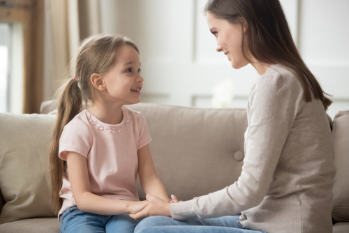 Mom talking to young daughter using positive parenting tips