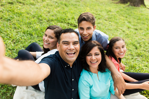 Father's Day - A happy latin family of five taking a selfie and smiling in a horizontal medium shot outdoors.