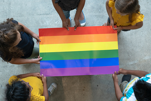 A group of multi-ethnic elementary students stand around a colorful gay pride poster. They are each holding an edge of the poster so it is out flat for the camera to see. Only the tops of their heads can be seen as the picture is taken from an aerial view. Each of the students are wearing casual clothing.
