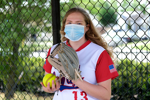 Youth Sports and COVID-19: Teenage girl in her softball uniform posing with a healthcare mask to protect her from the Coronavirus