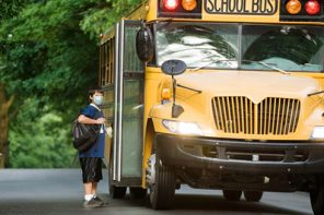 Reduce Germ spread: Boy in mask at school bus