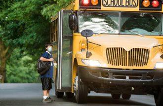 Reduce Germ spread: Boy in mask at school bus