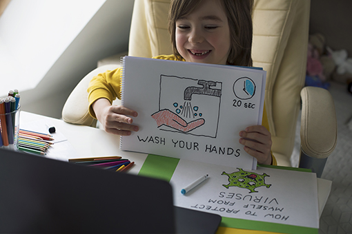 Child learning healthy habits in virtual school. He shares his drawing at home. Hand Sanitizer. E-learning. Coronavirus outbreak.