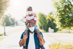 During COVID-19, the dad gives his young son a piggy back ride. They are both wearing protective masks.