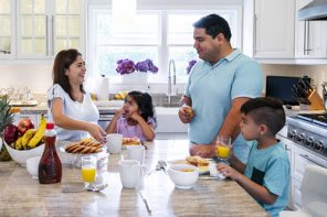 Reset Schedule - Hispanic parents enjoying breakfast with their young son and daughter in their kitchen.