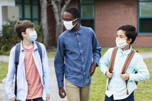 Back-to-school hacks: A multi-ethnic group of three middle school students walking and conversing outside the school building, carrying backpacks. The three boys are back to school during the COVID-19 pandemic, wearing protective face masks to help prevent the spread of coronavirus. The two shorter ones are brothers, mixed race Asian and Caucasian, 11 and 12 years old.