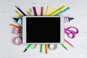 School tech accessories: tablet with an empty screen and office supplies on a white wooden background. Concept app for school children or online learning for children.